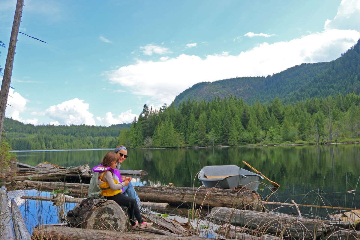 Kathleen Duborg and Bronny sit on the logs at Klein Lake